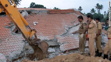 Indian officials look on as an excavator moves debris from a collapsed building after an explosion and fire at The Puttingal Devi Temple in Paravur early April 10, 2016.