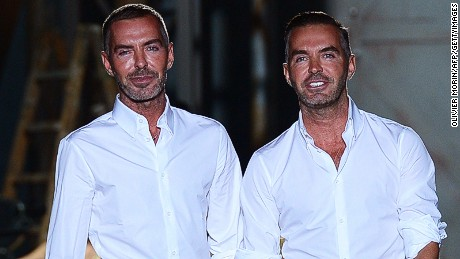 Designers Dean and Dan Caten acknowledge the audience at the end of the Dsquared2 Spring-Summer 2013 collection on September 24, 2012 during the Women's fashion week in Milan. AFP PHOTO / OLIVIER MORIN (Photo credit should read OLIVIER MORIN/AFP/GettyImages)