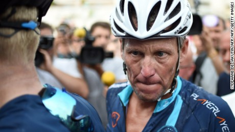 """US cyclist Lance Armstrong looks on upon his arrival in Rodez, southwest France, after riding a stage  of The Tour De France for a leukaemia charity, a day ahead of the competing riders, on July 16, 2015. For the first time since he was stripped of his seven Tour de France titles, disgraced cyclist Lance Armstrong rode a stage of the famous race for charity. Armstrong, 43, was riding a 198-kilometre (123-mile) stage a day ahead of the competing riders for a leukaemia charity but cycling officials have branded the exercise """"disrespectful"""". AFP PHOTO / STEPHANE DE SAKUTIN        (Photo credit should read STEPHANE DE SAKUTIN/AFP/Getty Images)"""
