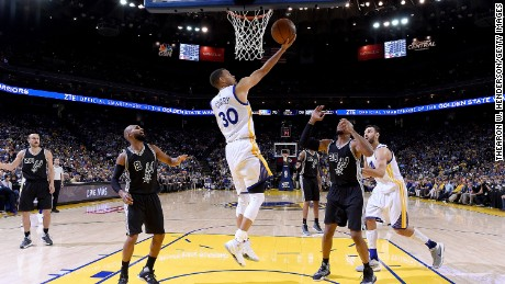 Stephen Curry #30 of the Golden State Warriors goes up to score on a reverse layup against the San Antonio Spurs in the third quarter of an NBA Basketball game at ORACLE Arena on April 7, 2016 in Oakland, California.