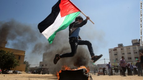 A Palestinian boy runs holding his national flag near a burning tyre as he acts out a scene for spectators visiting a building which used to be an Israeli prison where Palestinians were detained during Israel's occupation of Gaza on April 14, 2013. Hamas is organising tours of the facility which has been turned into a memorial centre. AFP PHOTO / MAHMUD HAMS        (Photo credit should read MAHMUD HAMS/AFP/Getty Images)