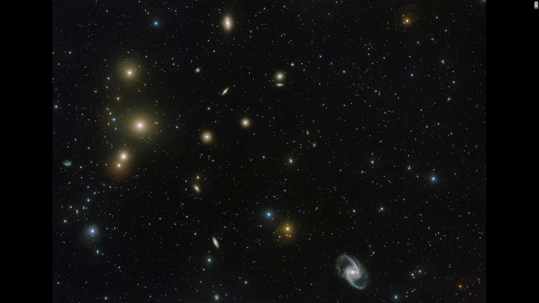 This image from the VLT Survey Telescope at ESO's Paranal Observatory in Chile shows a stunning concentration of galaxies known as the Fornax Cluster, which can be found in the Southern Hemisphere. At the center of this cluster, in the middle of the three bright blobs on the left side of the image, lies a cD galaxy -- a galactic cannibal that has grown in size by consuming smaller galaxies.