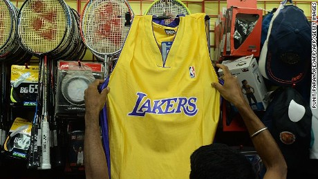 To go with 'Basket-Marketing-NBA-US-India' by John Biers In this photograph taken on May 12, 2015, an Indian sales assistant hangs a Los Angelese Lakers NBA team jersey at a sports accessories shop in Mumbai.  The NBA is forging ahead with plans for world domination, hoping that India will be the next Asian power to be seduced by hoop dreams after already captivating China. The landmark appearance of Sim Bhullar for the Sacramento Kings last month, the first player of Indian descent to score in the NBA, gave a fresh jolt to the league's bid to win over the cricket-mad nation of 1.3 billion.  AFP PHOTO/ PUNIT PARANJPE        (Photo credit should read PUNIT PARANJPE/AFP/Getty Images)