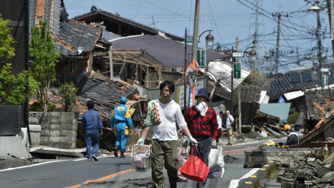Residents walk down a street on April 17 surrounded by destroyed homes in Mashiki, Japan.