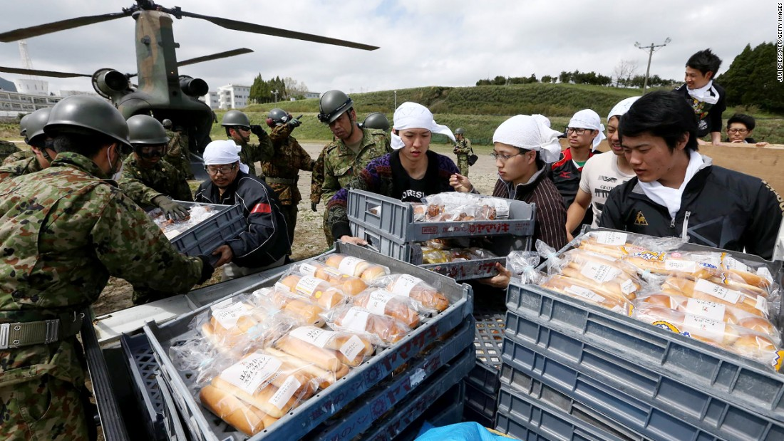 Students and soldiers unload food from helicopters  at the isolated Tokai University campus on April 17.