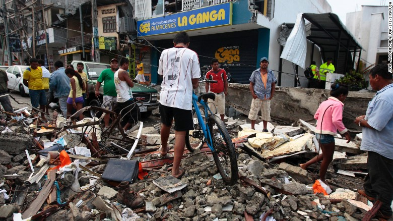 People walk among the debris of a collapsed building in Pedernales, Ecuador, on April 17.