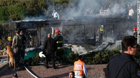 "Israeli security forces and emergency services gather around a burnt-out bus following an attack in Jerusalem on April 18, 2016. Police only said there was ""an attack"" without providing further details."