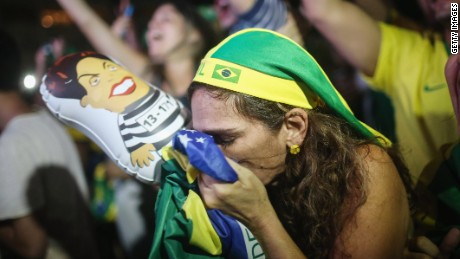 RIO DE JANEIRO, BRAZIL - APRIL 17: A pro-impeachment supporter kisses a Brazilian flag, while a live television broadcast, moments after lower house deputies voted to approve the motion to continue the impeachment process of President Dilma Rousseff on April 17, 2016 in Rio de Janeiro, Brazil. Rio will host the Rio 2016 Olympic Games in August. (Photo by Mario Tama/Getty Images)