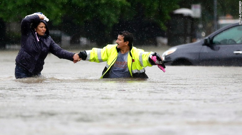 Alberto Lopez, right, helps his wife Glenda wade through floodwaters as they evacuate their flooded apartment complex Monday, April 18, 2016, in Houston. Storms have dumped more than a foot of rain in the Houston area, flooding dozens of neighborhoods and forcing the closure of city offices and the suspension of public transit. (AP Photo/David J. Phillip)