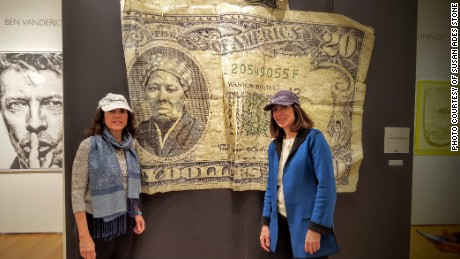 Barbara Ortiz Howard, left, and Susan Ades Stone, the women behind Women on 20s, an organization pushing for a woman on the $20 bill, stand before an artwork by Belgian artist Yann Guitton that was inspired by their  campaign. It was displayed recently at the Affordable Art Fair in New York City.