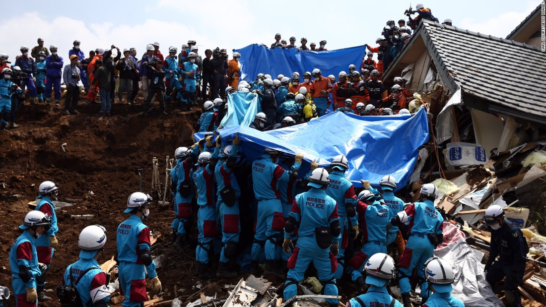 "Rescuers prepare to remove the body of a woman found in a house destroyed by a mudslide in Minamiaso on Tuesday, April 19, in the aftermath of a 7.0-magnitude quake on Kyushu Island. The same region was hit by a <a href=""http://www.cnn.com/2016/04/14/asia/japan-earthquake/"" target=""_blank"">6.2-magnitude quake</a> on Thursday, April 14."