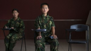 "China, Jinan, Shandong province, October 2015 -  Portrait of Xu Antai (center), 11 years old, and Jiang Yu (left), 14 years old, in a class of the ""Ya Bo center"", a military boot-camp for reeducation of young people who are by the majority suffering from excessive online game playing. Xu Antai has been living in the boot-camp for 4 months, and Jiang Yu for 6 months.   ><  Cina, Jinan, provincia dello Shandong, ottobre 2015 - Ritratto di Xu Antai, un bambino di 11 anni (centro), e di Jiang Yu (sinistra), una ragazza di 14 anni, in una classe presso il ""centro Ya Bo"", un boot-camp militare per la rieducazione di giovani problematici di cui la maggior parte soffre di un uso eccessivo di videogiochi online. Xu Antai vive nel centro da 4 mesi mentre Jiang Yu vive nel centro da 6 mesi."