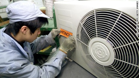 A worker sticks a trademark to a new air conditioner at Japanese Hitachi Household Electrical Appliances Company in Shanghai, 13 March 2003. AFPPHOTO/LIU Jin (Photo credit should read LIU JIN/AFP/Getty Images)