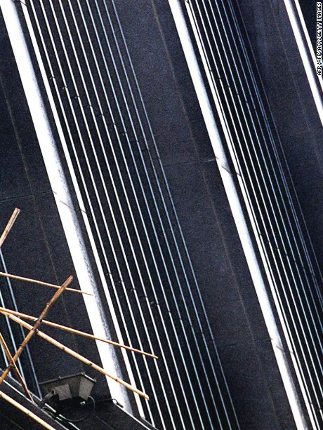 A man installs bamboo scalfolding on the high-tech metallic facade of a building in Hong Kong's Wanchai district 18 June. Buildings in the territory are installing special night-time lighting displays and making other preparations to celebrate Hong Kong's change of sovereignty from Britian to China midnight 30 June.   AFP PHOTO  Stephen SHAVER  (Photo credit should read STEPHEN SHAVER/AFP/Getty Images)