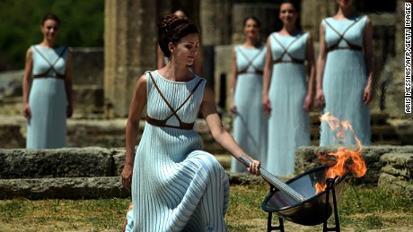 Actress Katerina Lechou acting the high pristess lights the Olympic flame at the Temple of Hera on April 21, 2016 during the lighting ceremony of the Olympic flame in ancient Olympia, the sanctuary where the Olympic Games were born in 776 BC.  The Olympic flame was lit Thursday in an ancient temple in one country in crisis and solemnly sent off carrying international hopes that Brazil's political paralysis will not taint the Rio Games that start in barely 100 days. / AFP / ARIS MESSINIS        (Photo credit should read ARIS MESSINIS/AFP/Getty Images)
