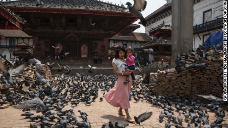 At Kathmandu's major attraction, in Durbar Square  a woman walks past pigeons where people come to feed them at the Pratap Malla statue. Bricks are seen stacked on the right from earthquake damage.