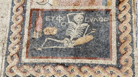 "A booze-swilling skeleton seen in this 2,400 year-old mosaic, discovered during excavations in Hatay. Turkey, advises ""be cheerful, enjoy your life."""