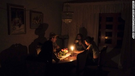 A family sit at a candlelit table in the state of Barinas, Venezuela on April 25.