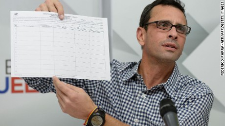 "Venezuelan opposition leader and Miranda State governor Henrique Capriles shows the form to activate the referendum on cutting President Nicolas Maduro's term short, during a press conference in Caracas on April 26, 2016. Tension in the recession-racked oil giant has reached the boiling point since the opposition won control of the National Assembly, the biggest threat yet to the socialist ""revolution"" launched by Maduro's late mentor Hugo Chavez in 1999. / AFP / FEDERICO PARRA        (Photo credit should read FEDERICO PARRA/AFP/Getty Images)"