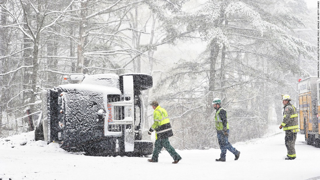 Fire and rescue personnel look at the scene of an overturned truck in Freeport, Maine, on Tuesday, April 26. No one was hurt, according to the Portland Press Herald.