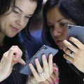 women playing on a smartphone