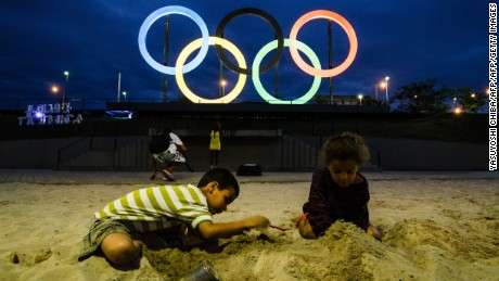 Children play with sand in front of the Olympic rings at Madureira Park, the third largest park in Rio de Janeiro, Brazil, on July 1, 2015, 400 days ahead of the Rio 2016 Olympic games. The 12-meter-high symbol was shipped from Great Britain after having decorated the Tyne Bridge in Newcastle during the 2012 London Olympic Games. AFP PHOTO / YASUYOSHI CHIBA        (Photo credit should read YASUYOSHI CHIBA/AFP/Getty Images)