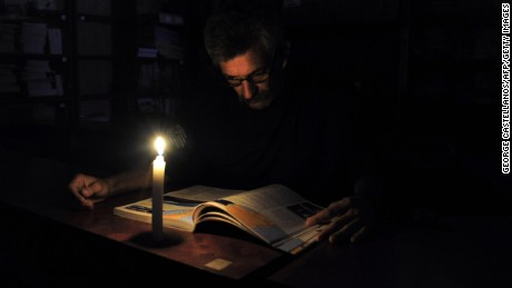 A man reads with a candle's light during a power cut in the border state of San Cristobal, Venezuela, 600 km west of Caracas on April 25, 2016.