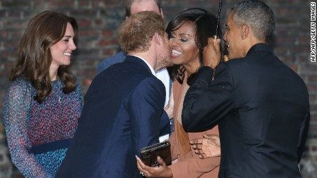 Britain's Prince Harry (2L) kisses US First Lady Michelle Obama (2R) as he and Prince William, Duke of Cambridge (C) and Catherine Duchess of Cambridge (L) greet US President Barack Obama (2R) and the First Lady for dinner at Kensington Palace in London, April 22, 2016.