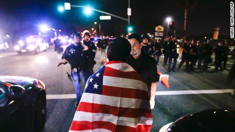 Protestors are pushed off the street by law enforcement after a rally for Republican presidential candidate Donald Trump, Thursday, April 28, 2016 in Costa Mesa, Calif. (AP Photo/Chris Carlson)