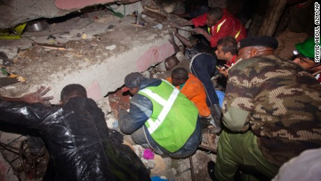 Rescue personnel search for survivors at the site of a building collapse in Nairobi, Kenya, Saturday, April 30, 2016. A six-story residential building in a low income area of the Kenyan capital collapsed Friday under heavy rain and flooding, trapping an unknown number of people in the rubble, Kenyan officials said.(AP Photo/Sayyid Abdul Azim)