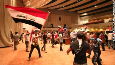 """Iraqi protesters wave national flags as they gather inside the parliament after breaking into Baghdad's heavily fortified """"Green Zone"""" on April 30, 2016.  A protest held outside the Green Zone escalated after parliament again failed to reach a quorum and approve new ministers to replace the current government of party-affiliated ministers. / AFP / HAIDAR MOHAMMED ALI        (Photo credit should read HAIDAR MOHAMMED ALI/AFP/Getty Images)"""