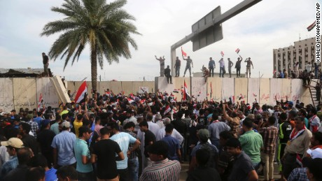 Supporters of Shiite cleric Muqtada al-Sadr walk over the blast walls surrounding Baghdad's highly fortified Green Zone Saturday, April 30, 2016. Dozens of protesters climbed over the blast walls and could be seen storming the Parliament building, carrying Iraqi flags and chanting against the government. (AP Photo/Khalid Mohammed)