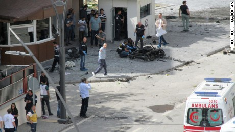 Police officers examine the scene outside the police headquarters in Gaziantep, Turkey, following a car bomb blast.