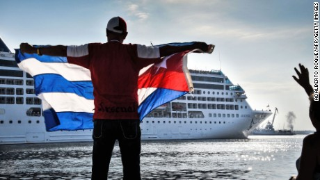 A man waves a Cuban flag at the Malecon waterfront as the first US-to-Cuba cruise ship to arrive in the island nation in decades glides into the port of Havana, on May 2, 2016. The first US cruise ship bound for Cuba in half a century, the Adonia -- a vessel from the Carnival cruise's Fathom line -- set sail from Florida on Sunday, marking a new milestone in the rapprochement between Washington and Havana. The ship -- with 700 passengers aboard -- departed from Miami, the heart of the Cuban diaspora in the United States. / AFP / ADALBERTO ROQUE        (Photo credit should read ADALBERTO ROQUE/AFP/Getty Images)