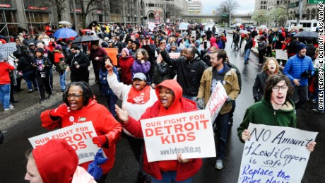 Members of the Detroit Federation of Teachers march down Grand Blvd., during a rally in front of the Detroit Public Schools offices in Detroit, Monday, May 2, 2016. The district's state-appointed transition manager Steven Rhodes says 45,628 of approximately 46,000 students were forced to miss classes Monday as 1,562 teachers called in sick. Detroit's schools are expected to be out of cash starting July 1.  (Daniel Mears/The Detroit News via AP)