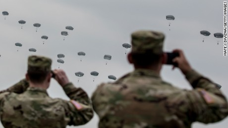GRAFENWOEHR, GERMANY - APRIL 12:  U.S. soldiers look at paratroopers from the U.S. Army 173rd Airborne Brigade, the UK's 16 Air Assault Brigade and Italian Folgore Airborne Brigade as they parachute to the ground during a training jump as part of the Saber Junction 16 military exercises near the Hohenfels Training Area on April 12, 2016 near Grafenwoehr, Germany. More than 1,200 paratroopers participated in the jump, one of the biggest airborne training operations in Europe this year. Saber Junction 16, taking place from March 31 to April 24, is the U.S. Army Europe's largest combat training in 2016 and nearly 5,000 participants from 16 NATO and European partner nations are taking part in the exercise. The U.S. military conducts training exercises with NATO-member armed forces as well as partner nations, many of them eastern European nations, on a regular basis.  (Photo by Matej Divizna/Getty Images)