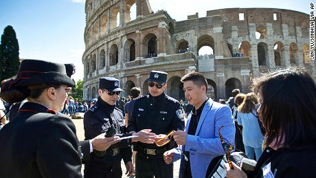 In this Monday, May 2, 2016 photo released by China's Xinhua news agency, Chinese police Shu Jian, third from left, and Sa Yiming, second from left, together with two Italian police officers, check documents of a Chinese tourist group outside the Colosseum in Rome. Chinese policemen are in Italy to start patrols with Italian officers in Rome and Milan in a two-week experiment. (Jin Yu/Xinhua via AP)