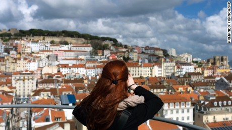 A woman takes pictures from the top of Lisbon's Santa Justa lift Tuesday, April 19 2016. The originally steam-powered lift inaugurated in 1901 is a national monument popular for tourists and it offers a 360-degree view of the city's old center and surrounding hills. (AP Photo/Armando Franca)