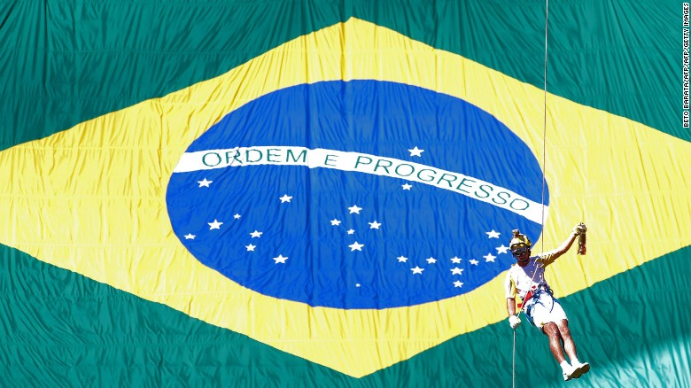 Brazilian fireman Haudson Alves descends from a helicopter carrying the Olympic flame on a lantern at the Brasilia National Stadium in Brasilia on May 3, 2016. Embattled President Dilma Rousseff greeted the Olympic flame in Brazil on Tuesday, promising not to allow a raging political crisis, which could see her suspended within days, to spoil the Rio Games. The torch will now be carried in a relay by 12,000 people through 329 cities, ending in Rio's Maracana stadium on August 5 for the opening ceremony.        / AFP / BETO BARATA        (Photo credit should read BETO BARATA/AFP/Getty Images)