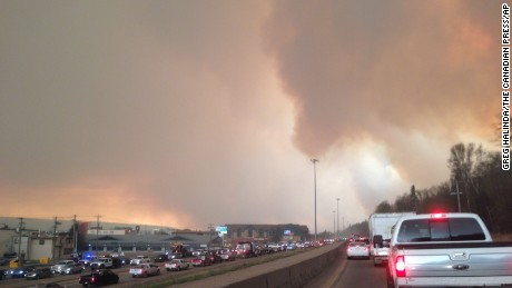 Smoke from a wildfire rises in the air as cars line up on a road in Fort McMurray, Alberta.