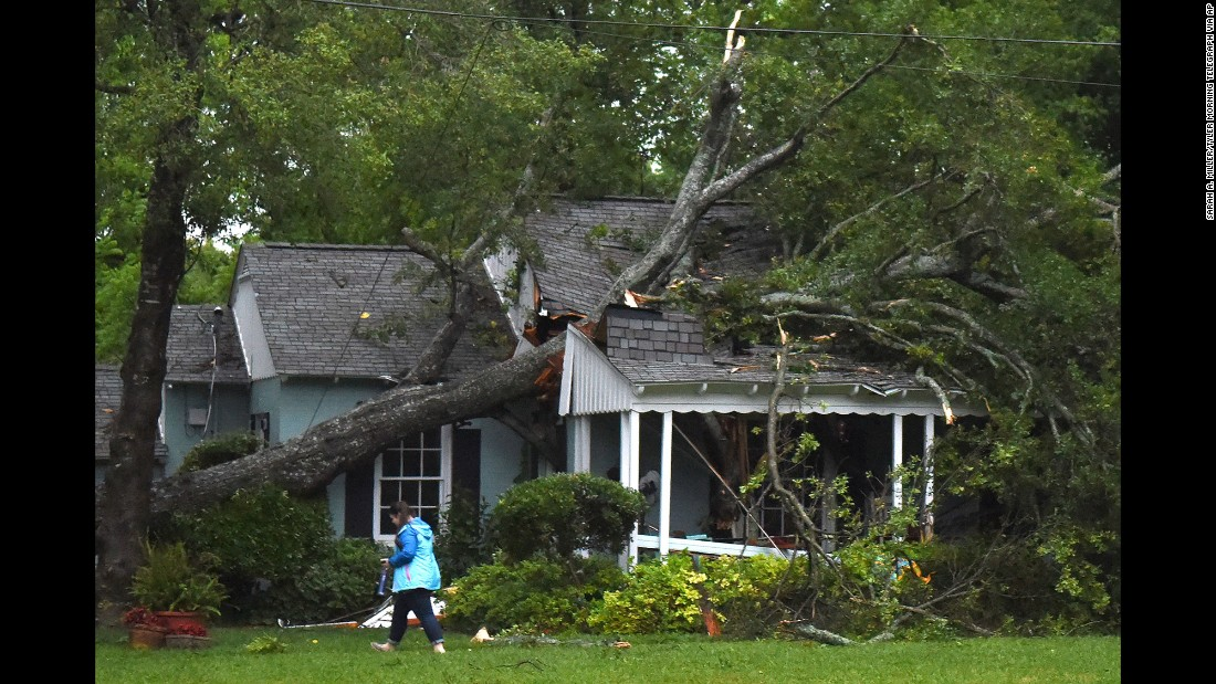 A woman walks past a house damaged by a fallen tree during storms in Lindale, Texas, on Friday, April 29.