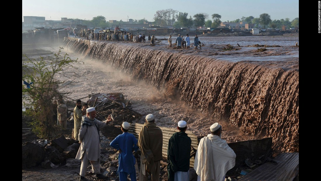 People cross a flooded street following heavy rain on the outskirts of Peshawar, Pakistan, on Monday, April 4.