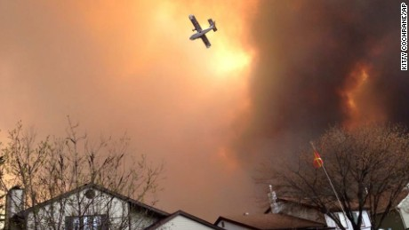 Smoke fills the air as a small plane flies overhead in Fort McMurray, Alberta, Tuesday, May 3, 2016.