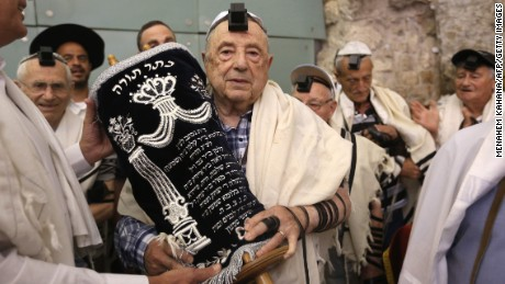 Dozens of Jewish holocaust survivors wear the Tefilin or the Phylacteries and the Tallit prayer shawl as they dance with the Torah after performing their Bar-Mitzvah Jewish ceremony, normally done at the age of 13-years-old, on May 2, 2016, at the Western Wall in the Jerusalem's Old City. Some 50 male and female holocaust survivors were invited to perform the Jewish Bar-Mitzvah ceremony some 70 years after World War II. / AFP PHOTO / MENAHEM KAHANAMENAHEM KAHANA/AFP/Getty Images