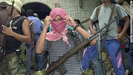 JOLO, PHILIPPINES:  (FILES) Dated 27 May 2000 file picture shows Al-Qaeda linked Abu Sayyaf gunmen guard a mosque in Bandang village, Jolo island where their leaders and group of negotiators meet for the release of 21 Asian and Western hostages.  Jolo, one of the Philippines southernmost islands boasts rich land and marine natural resources but serious peace and order problems have left the island mired in poverty. The Tausogs, the native Muslim tribes who make up the majority have  tradition for fierce martial courage and fondness for weaponry which has helped fuel the frequent explosions of violence in Jolo ranging from Muslim separatist wars, mass kidnapping campaigns, clan feuds and political disputes.   AFP PHOTO    ROMEO GACAD  (Photo credit should read ROMEO GACAD/AFP/Getty Images)