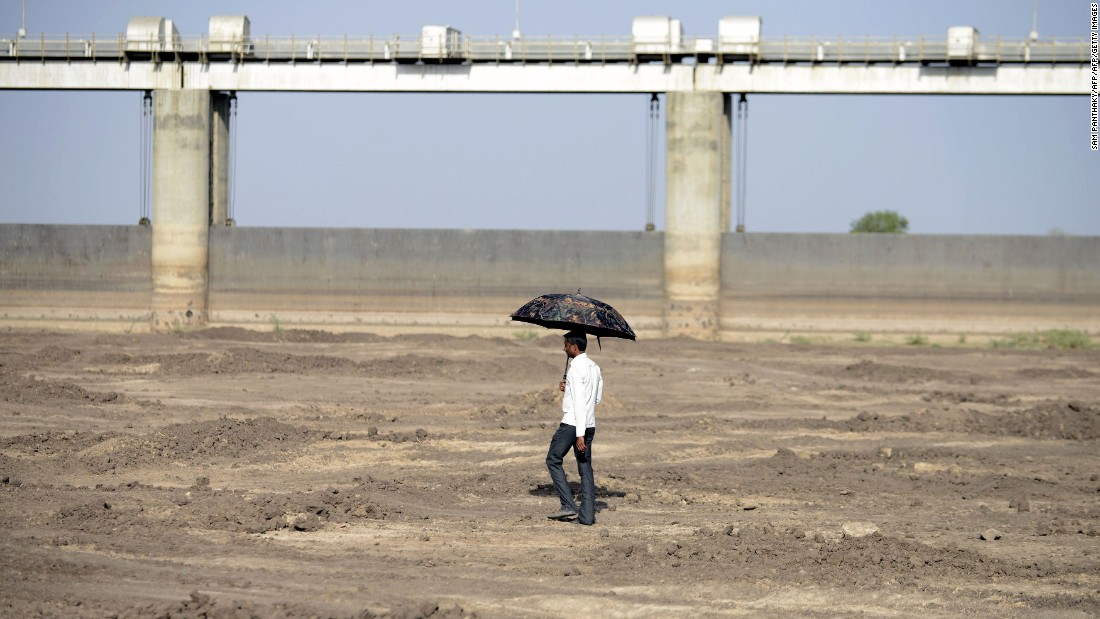 A man walks on the dry reservoir bed next to Gunda Dam in India's western Gujarat state on Friday, April 1.
