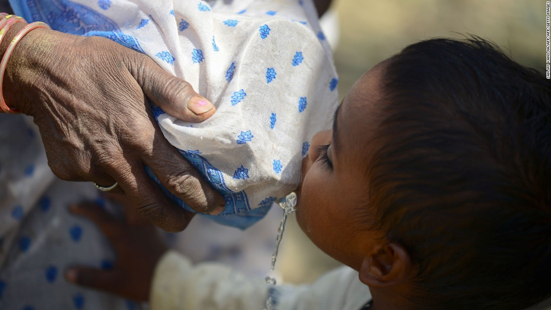 A woman tries to filter water with her sari as a child drinks in the Shankargarh area on April 21.