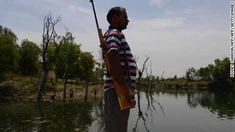In this photograph taken on April 27, 2016, a gunman stands alert at a water reservoir in Tikamgarh in the central Indian state of Madhya Pradesh.  Armed men have been securing the Barighat dam for months against water thefts by desperate farmers from neighbouring state to ensure supply of potable water to thousands of residents of Tikamgarh district in Madhya Pradesh state. Tikamgarh is part of central India's parched Bundelkhand region -- consisting of 13 districts, half of which lie in neighbouring Uttar Pradesh state- which is reeling from years of below-par monsoon rains. Officials say the ground water level has receded more than 100 feet in past few years as the area has been receiving less than half of the average annual rains.  / AFP / MONEY SHARMA / TO GO WITH AFP STORY INDIA-WEATHER-DROUGHT,FOCUS BY JALEES ANDRABI         (Photo credit should read MONEY SHARMA/AFP/Getty Images)