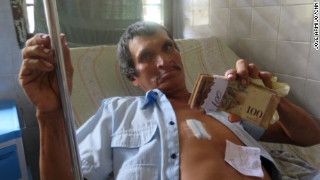 Venezuelan hospital patient Jose Luis Vasquez shows the money he keeps on him to pay for treatment and supplies.