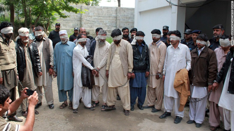 Police escort blindfolded suspects accused in the teen's killing to court Thursday in Abbottabad.